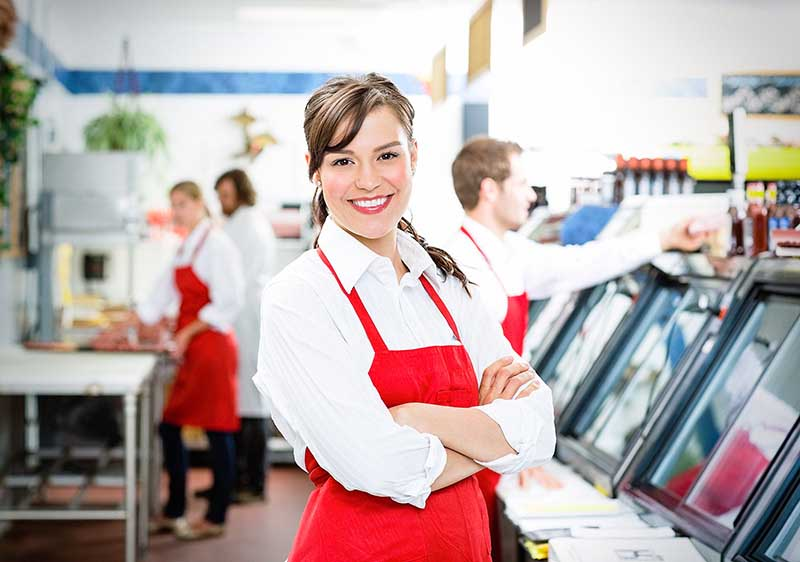 woman smiling behind food counter