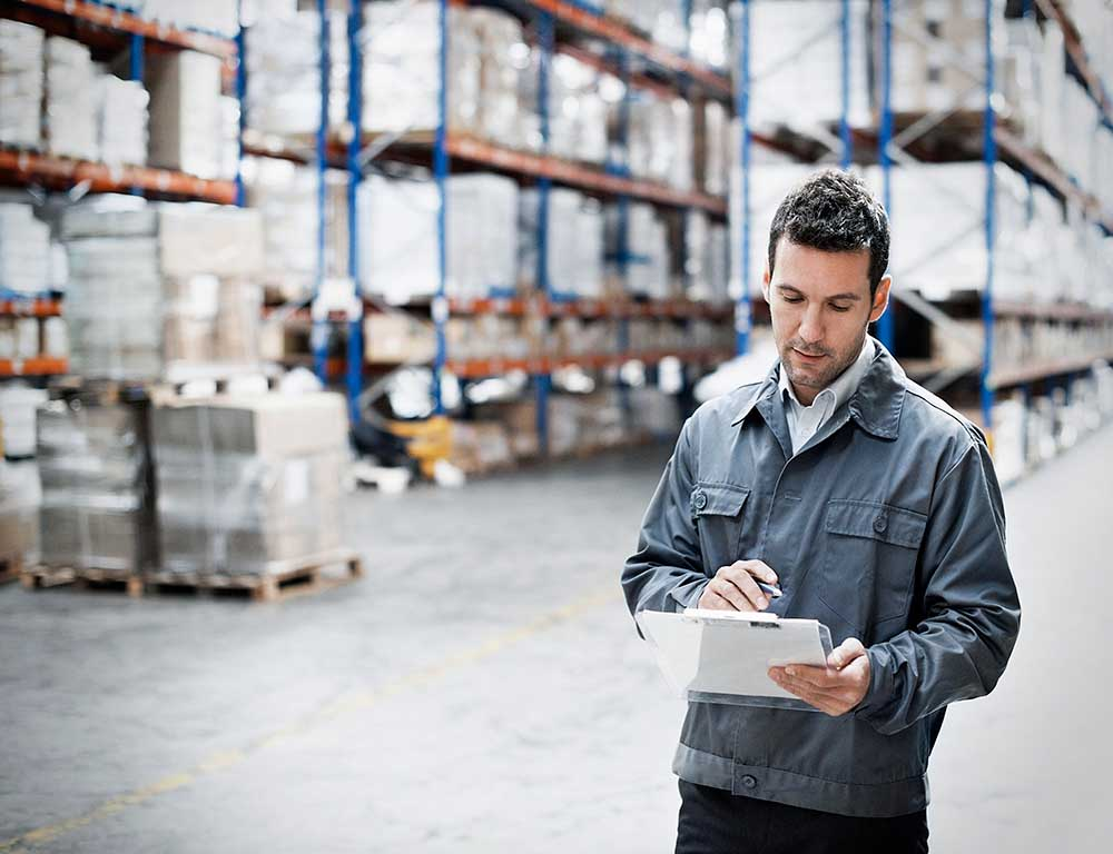 man taking notes in a warehouse